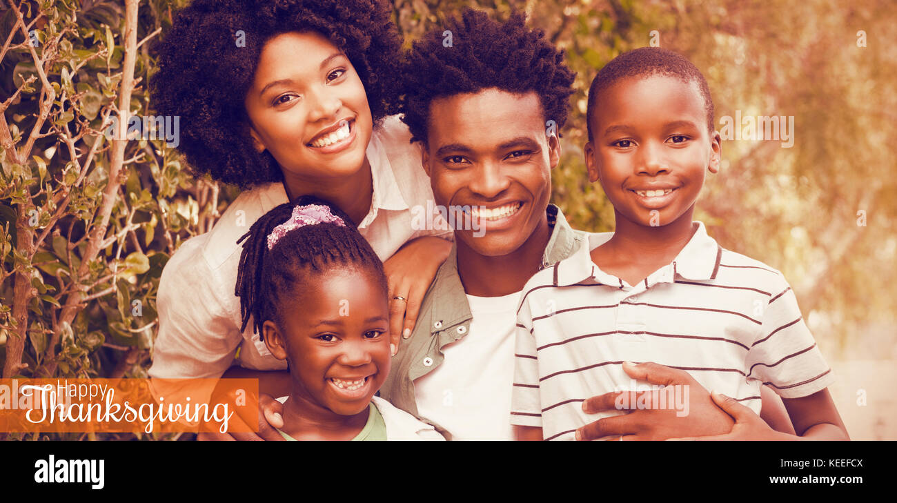 Thanksgiving greeting text against happy family smiling at camera - Stock Image