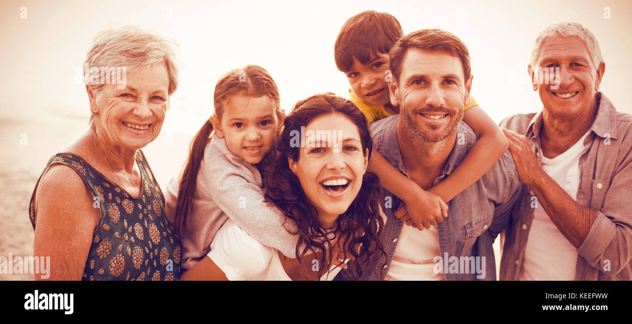 Portrait of smiling happy family posing at beach - Stock Image
