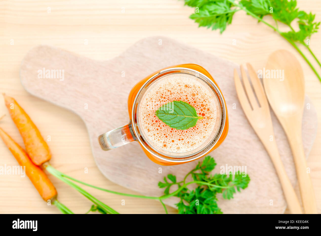 Glasses of carrot juice with carrot roots on wooden background.Glasses of tasty fresh carrot juice.Carrot juice - Stock Image