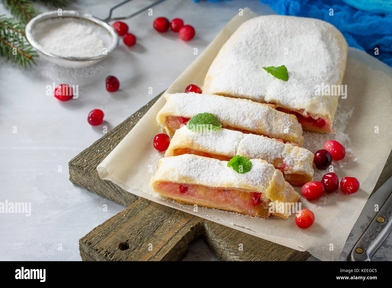 Homemade apple strudel with fresh apples, cranberry and sugar powder on slate or stone background. - Stock Image