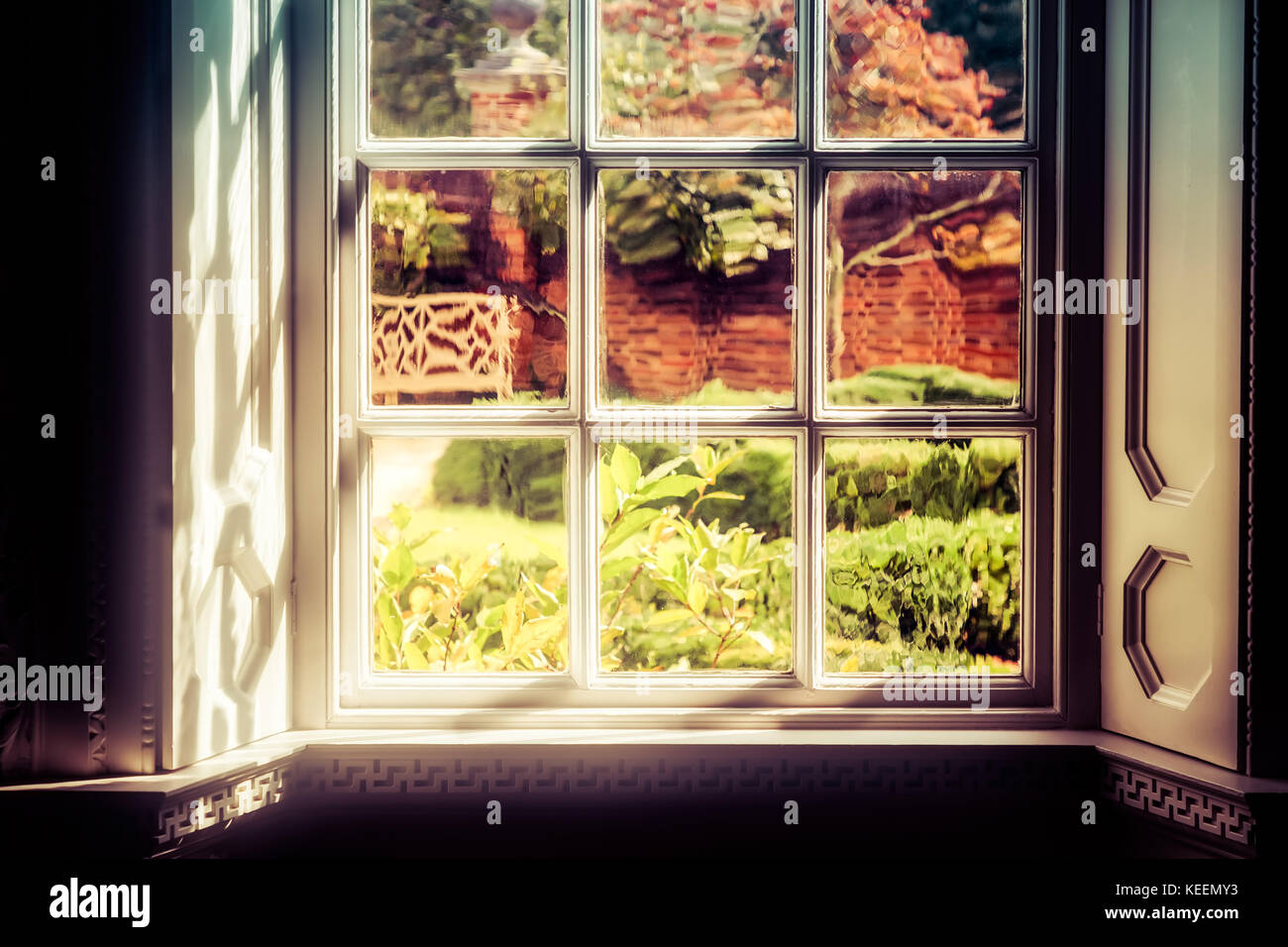 The shadows and light hitting a window that looks in to a Virginia yard. - Stock Image