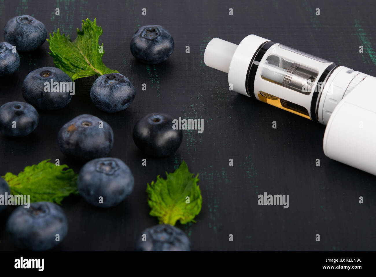 white electronic cigarette on a dark table, next to a scattered berry - Stock Image