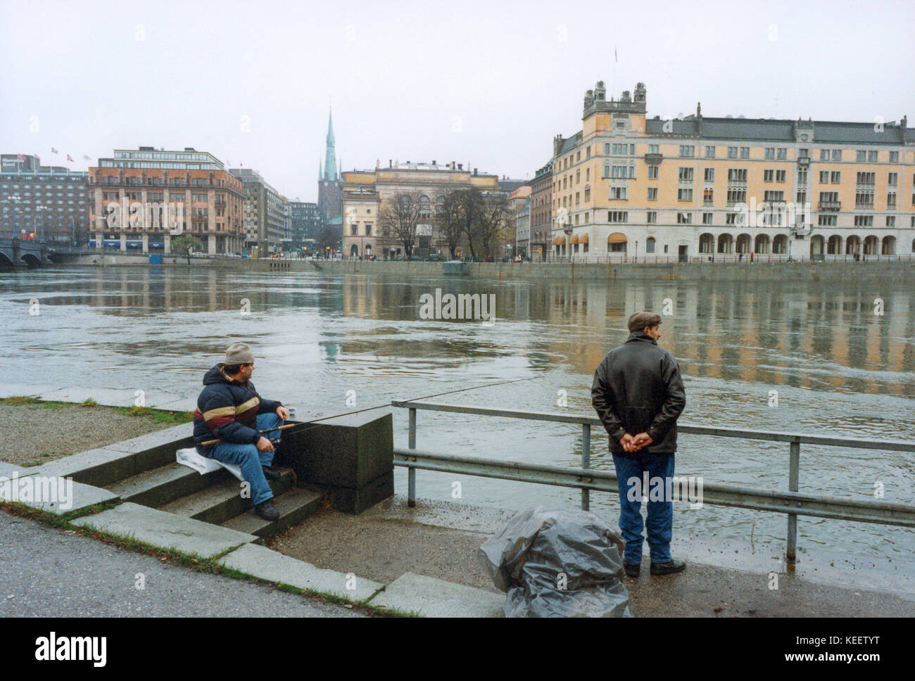Two men fishing in Stockholm City center opposite The Government buildings 2010 - Stock Image