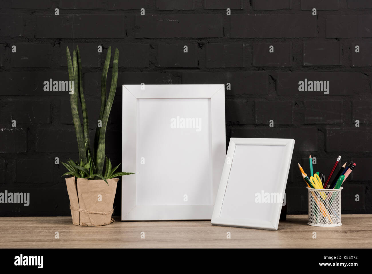 close up view of empty photo frames, pencils and plant in flowerpot ...