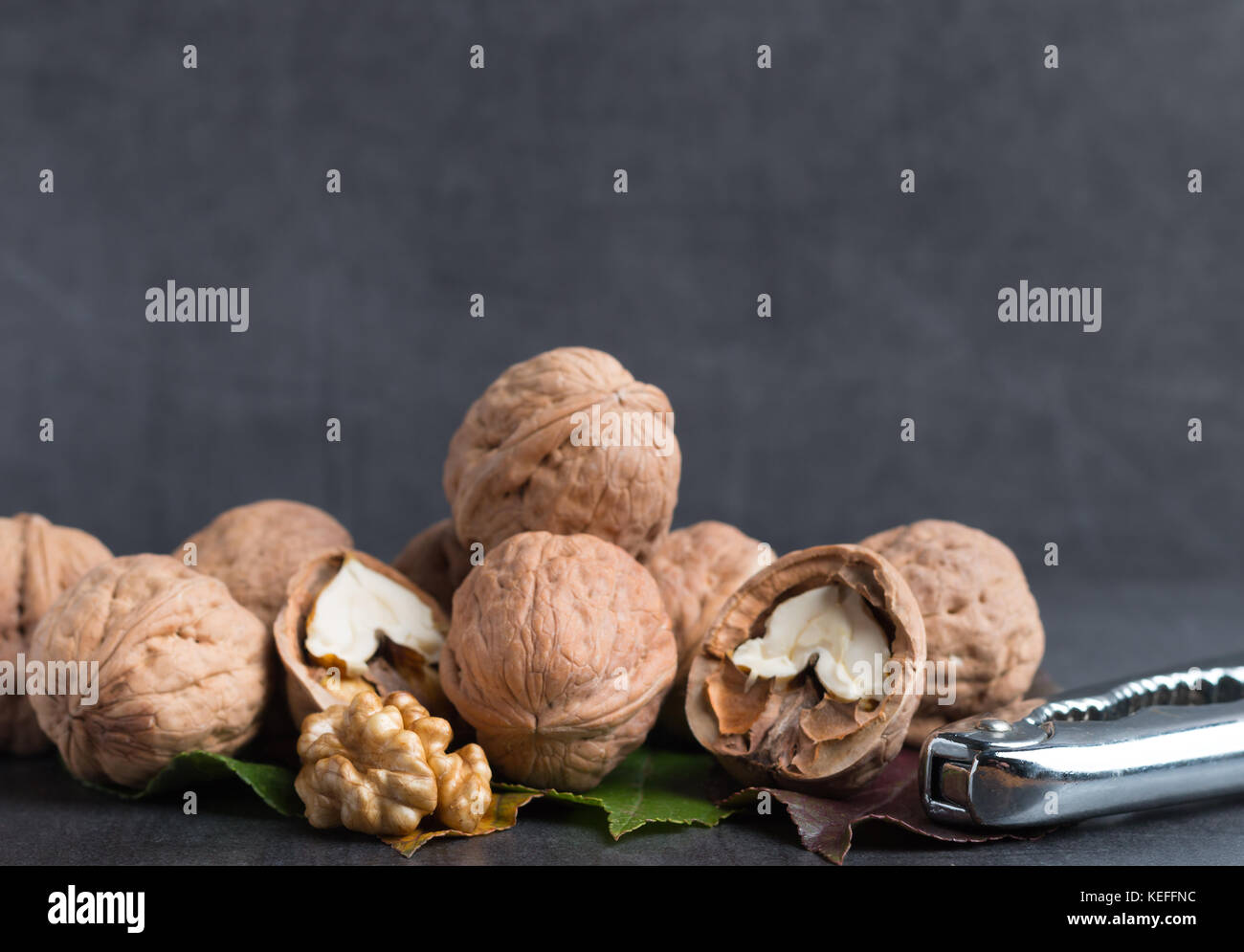 bio walnuts on a stone table with a nutcracker - Stock Image