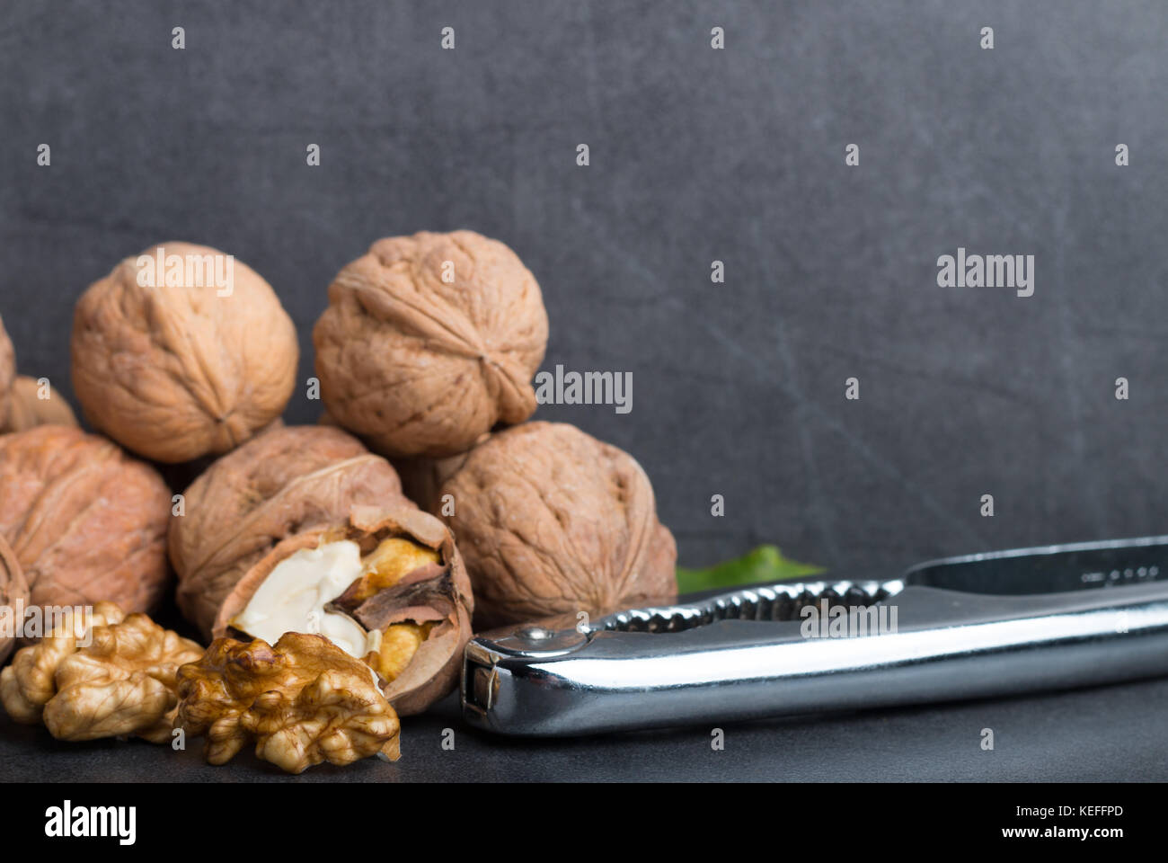 bio walnuts on a stone table with a nutcracker front view - Stock Image