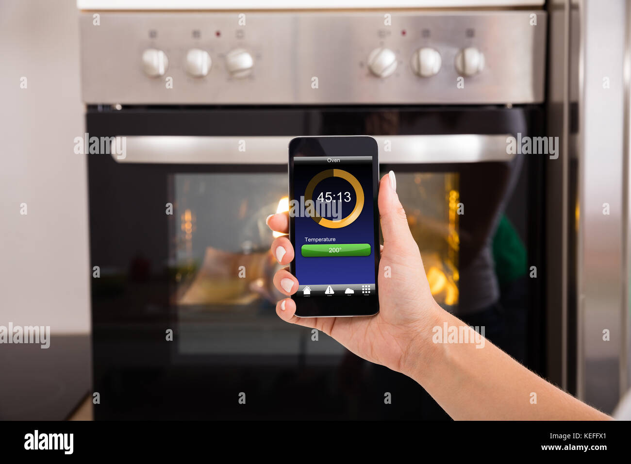 Close-up Of Person Hands Operating Oven Appliance With Mobile Phone - Stock Image