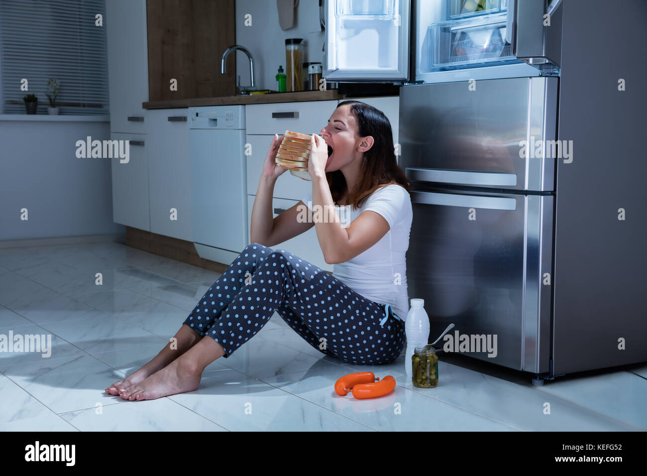 Young Woman Eating Sandwich With Jar Of Pickle While Sitting On ...