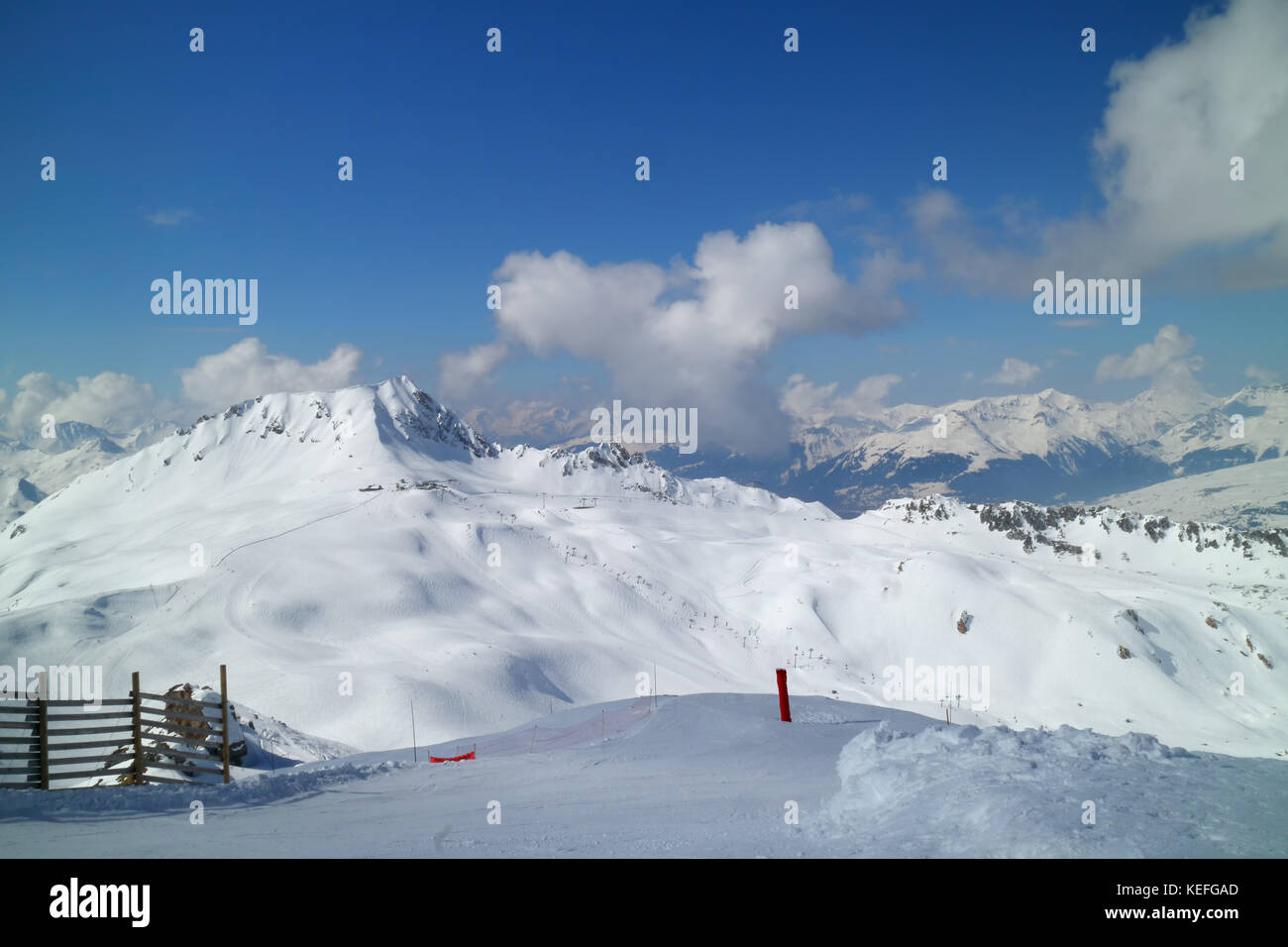 Alpine rugged snowy peaks panorama with skiing slopes in Les Arcs resort, Alps, France - Stock Image