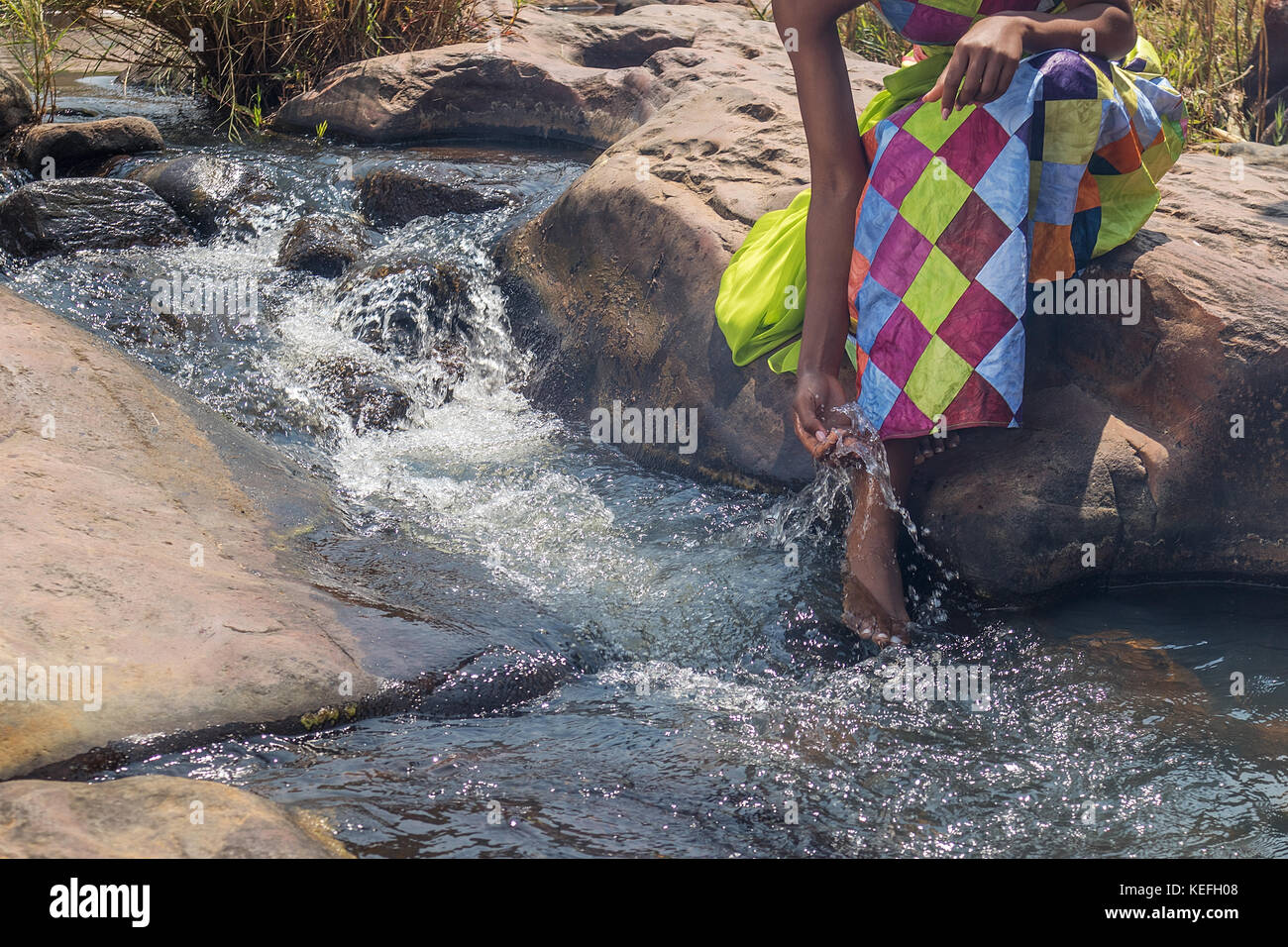 Woman in African outfit on the verge of fluent river. Interacting with water. Angola. Stock Photo