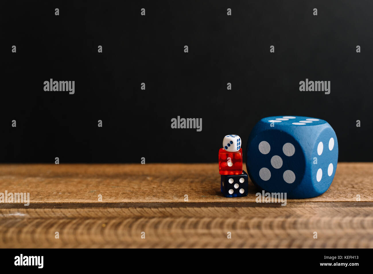dice on a wooden table black background. - Stock Image