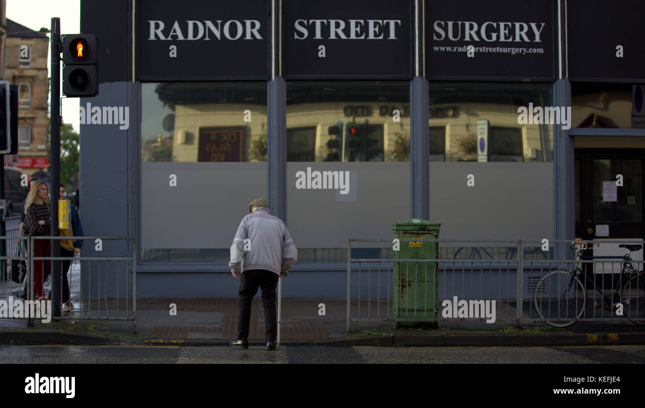 senior citizen man old people in Glasgow city centre Radnor Street Surgery struggle to cross streets in time because - Stock Image