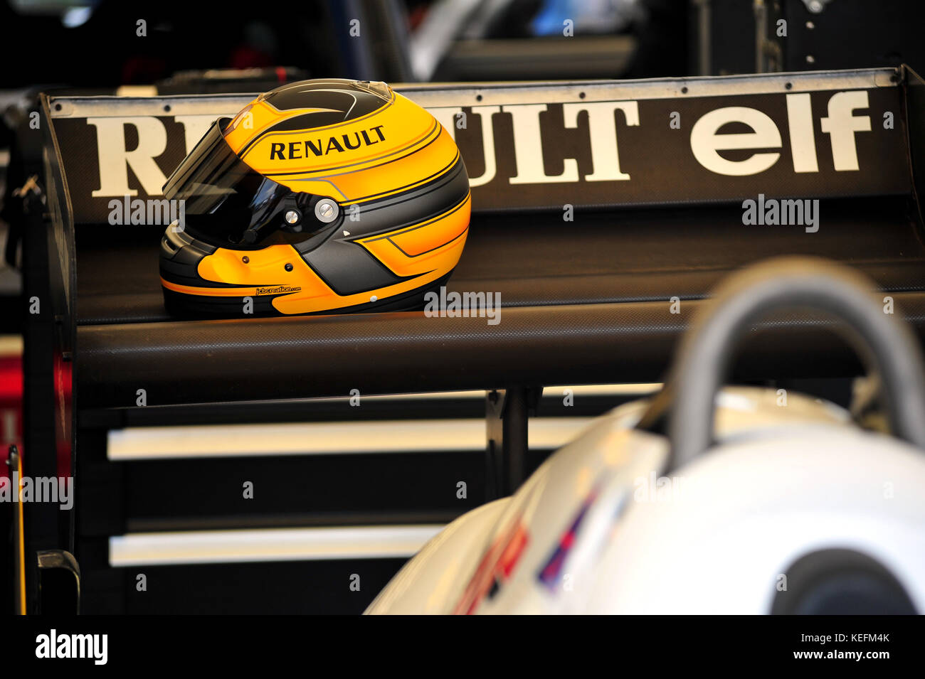 A Yellow racing helmet on the rear wing of an F1 car - Stock Image