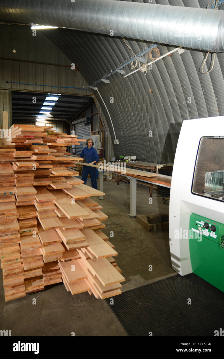 GREYMOUTH, NEW ZEALAND, 18 JULY, 2017: Workers use a four sider machine to plane rough edges from four sides of - Stock Image