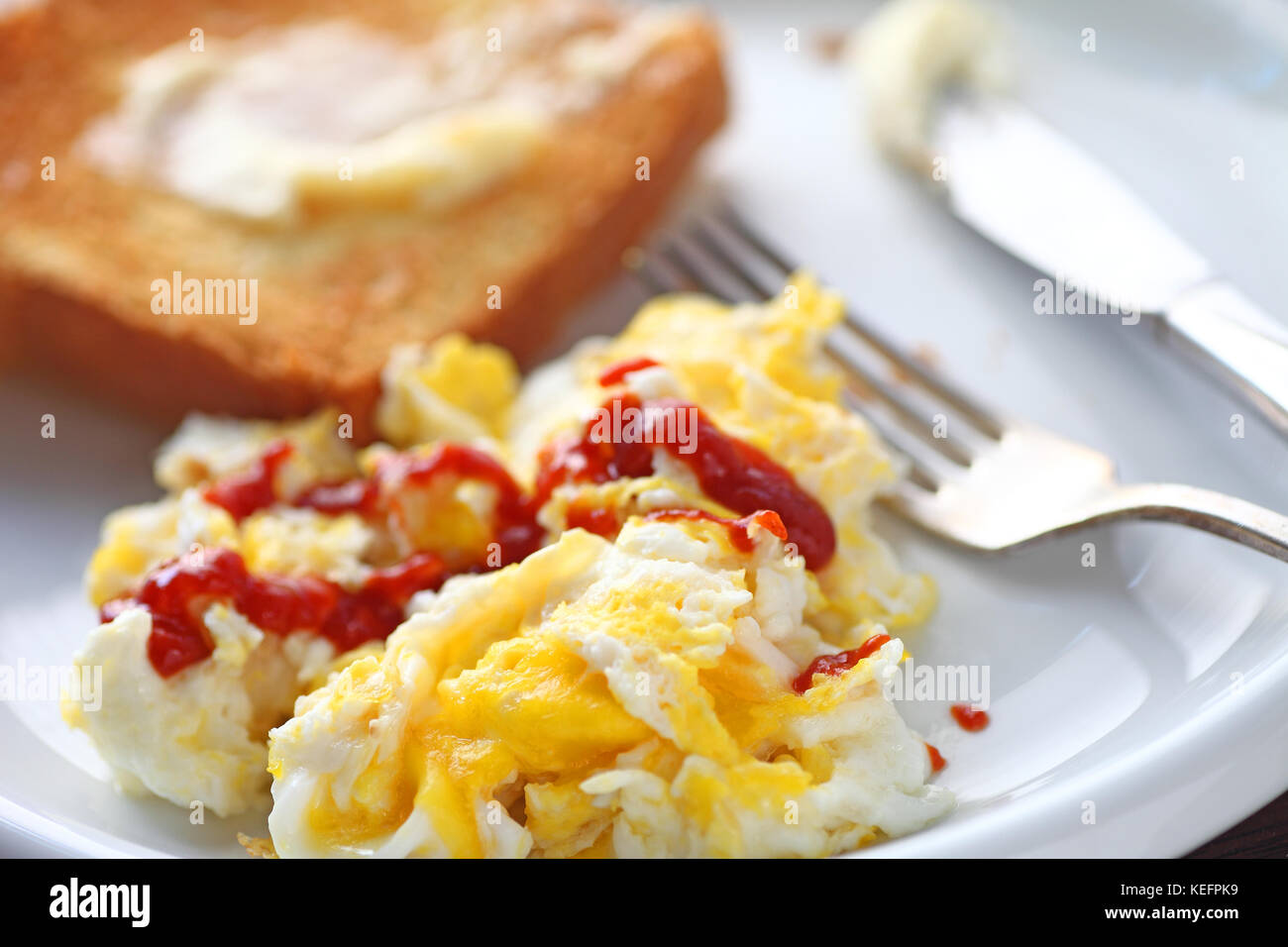 Scrambled eggs with Sriracha hot chili sauce and buttered toast - Stock Image