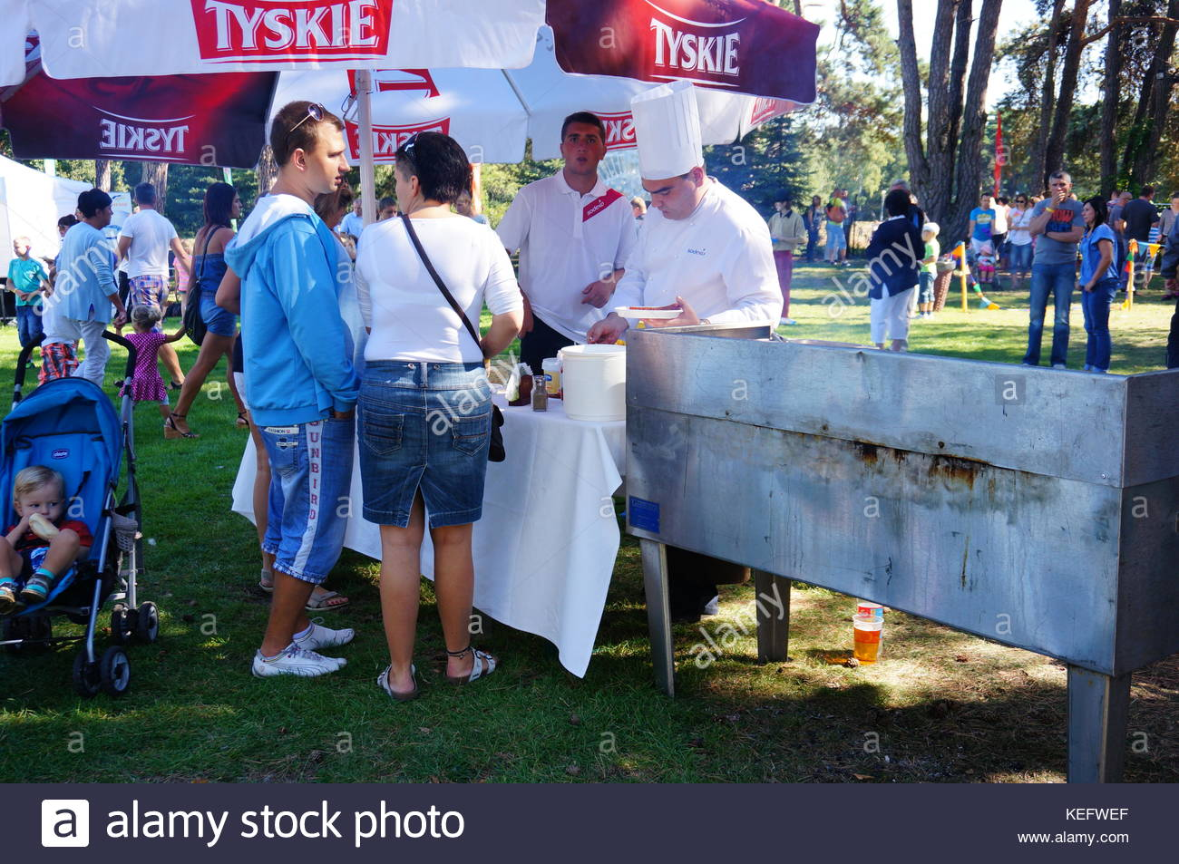 POZNAN, POLAND - SEPTEMBER 07, 2013: People by a barbeque stand at a Unilever employee event - Stock Image