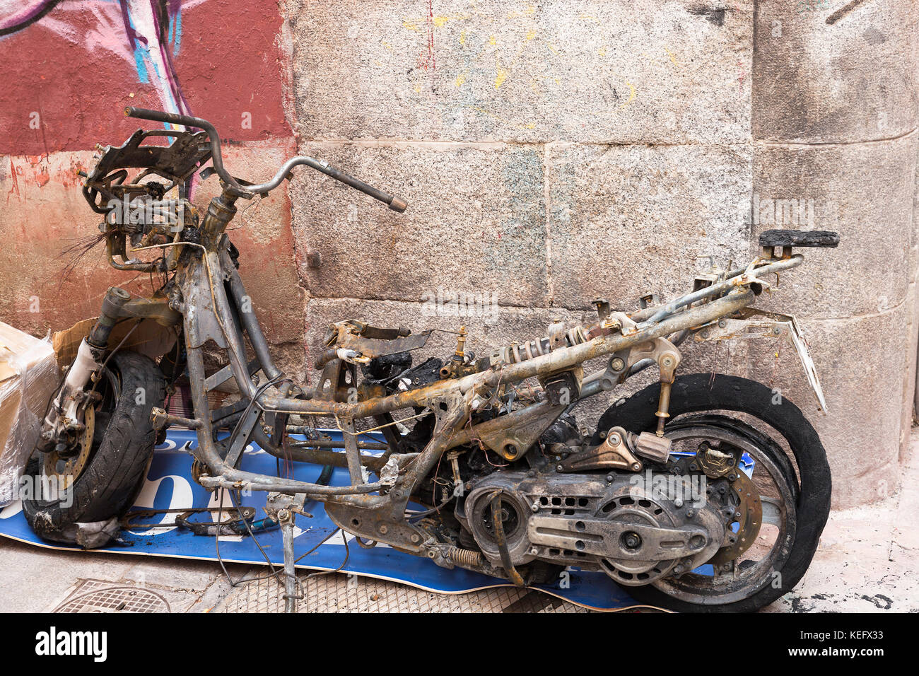 Burnt motorcycle in the street rested on a wall. Vandalism action - Stock Image