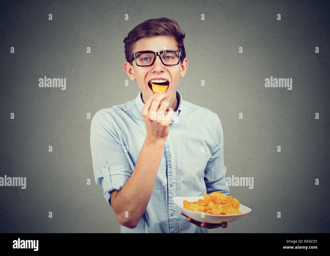 Young man eating potato chips - Stock Image