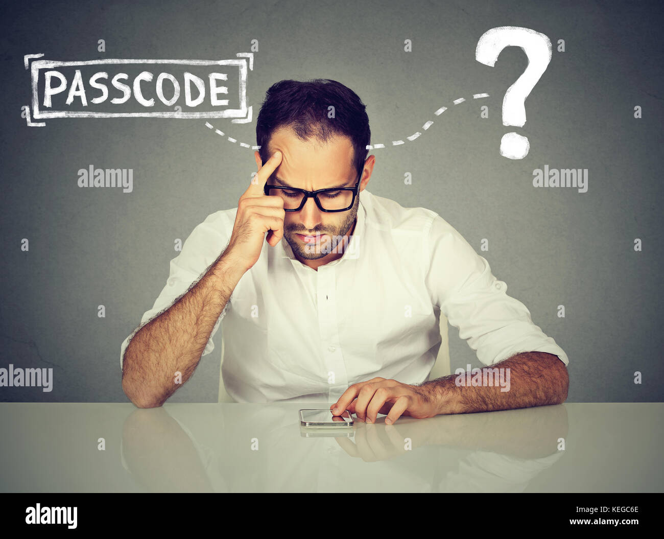 Desperate young man trying to log into his smart phone forgot password - Stock Image