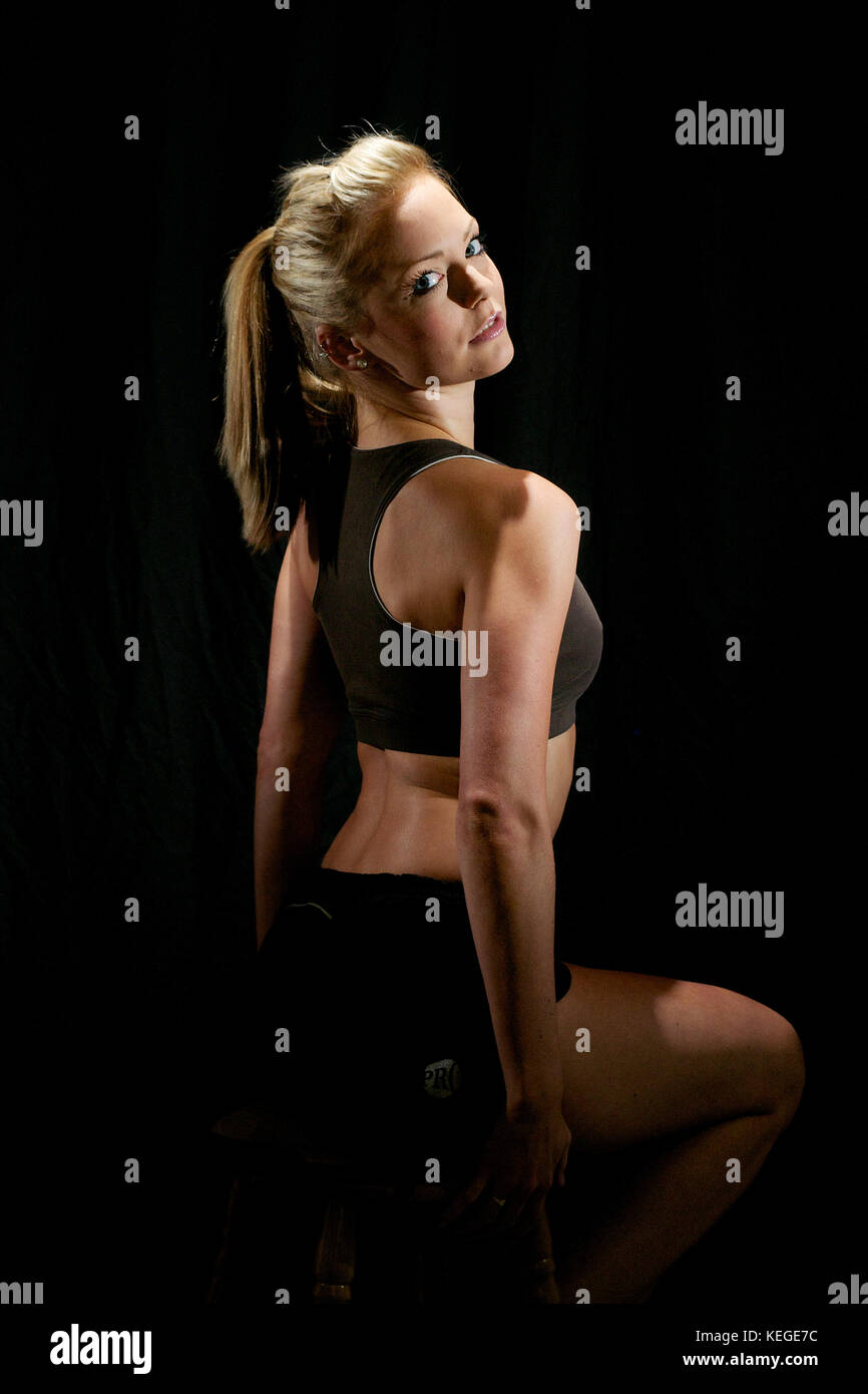 Beautiful blonde girl in keep-fit outfit and working out in a studio - Stock Image