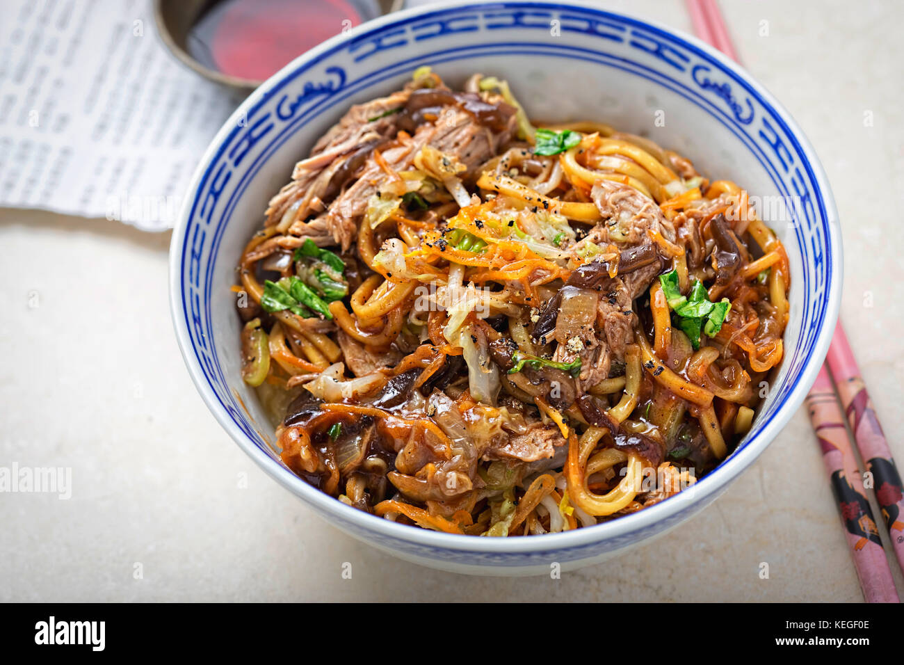 Hoisin duck noodles. Egg noodles with strips slow roasted duck in hoisin sauce with oak choi. - Stock Image