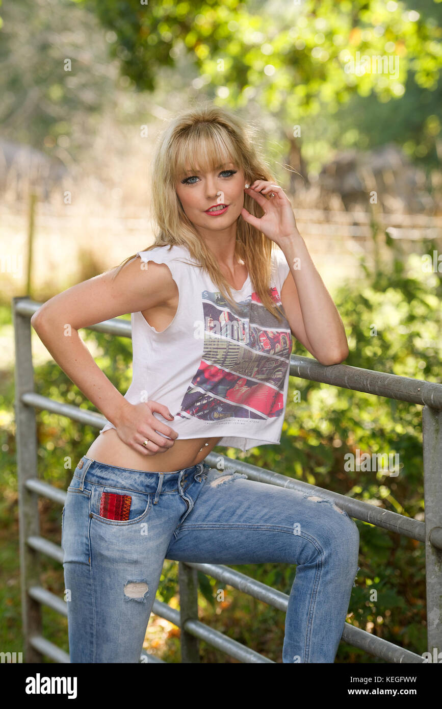 b7f0caa038a Beautiful blonde girl wearing jeans and a white t-shirt in the countryside