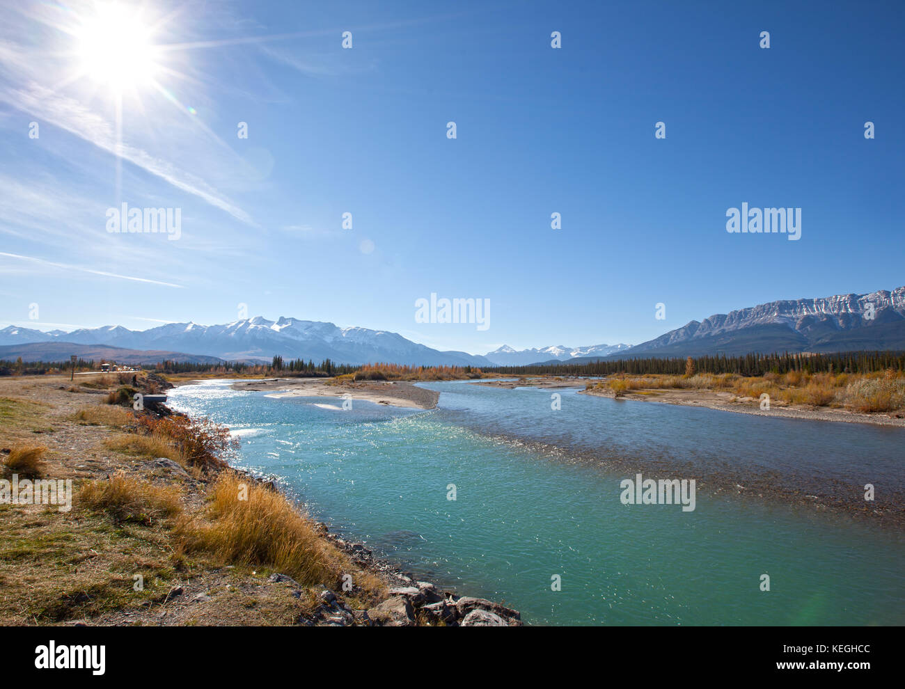 the turquoise Athabasca river with blue sky and sun flare in Jasper National Park, Alberta - Stock Image