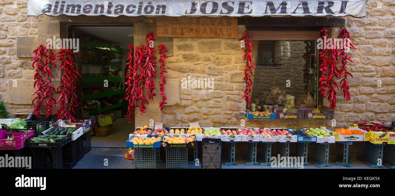 Red chillies, fresh vegetables and fruit displayed outside Alimentacion Jose Mari food shop in Laguardia, Rioja - Stock Image