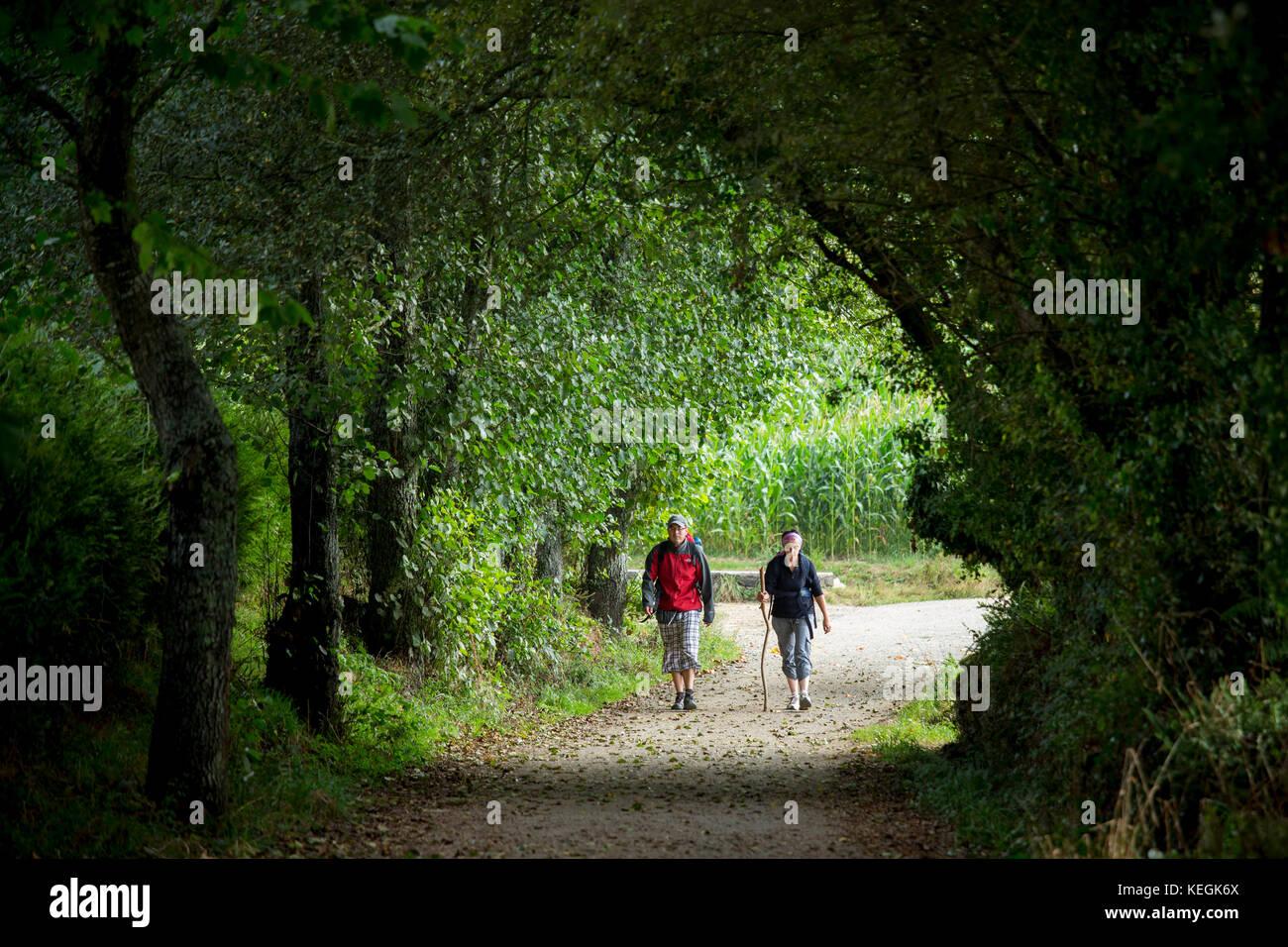 Pilgrim couple on the Camino de Santiago PIlgrim's Way to Santiago de Compostela in Galicia, Spain - Stock Image