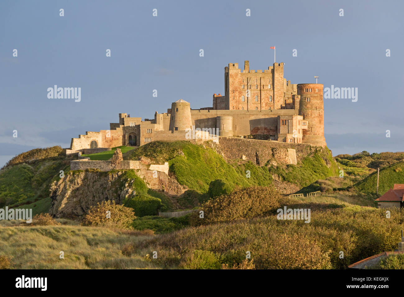 Evening light over Bamburgh Castle, Bamburgh, Northumberland, England, UK - Stock Image