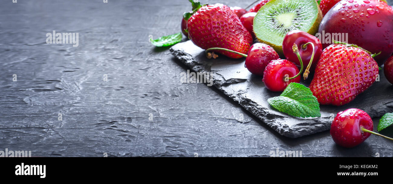 Mix of Juicy summer fruits and berries. Strawberry, cherry, kiwi and peaches on black slate plate. Long banner format - Stock Image