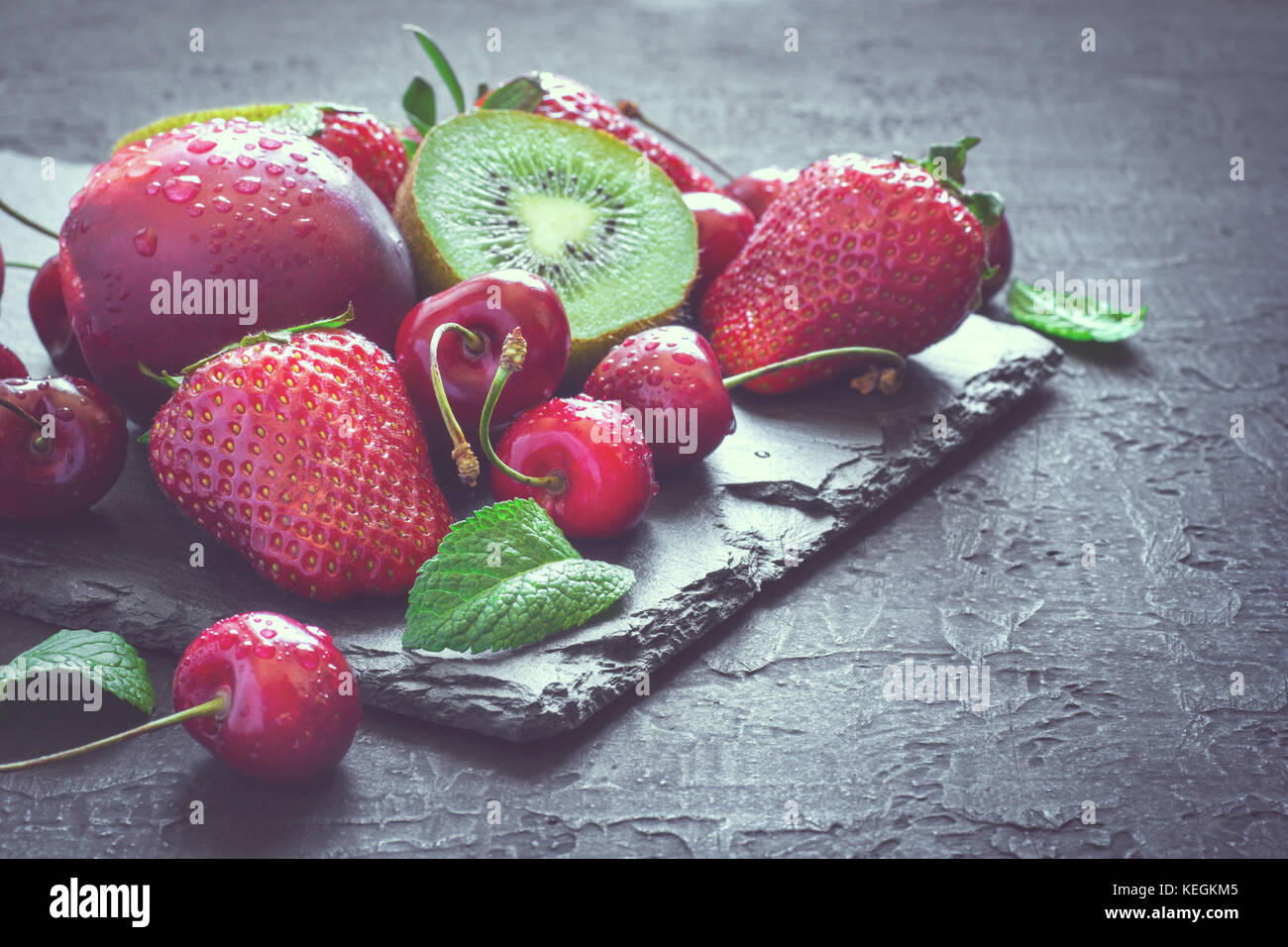 Mix of Juicy summer fruits and berries. Strawberry, cherry, kiwi and peaches on black slate plate. Toned - Stock Image