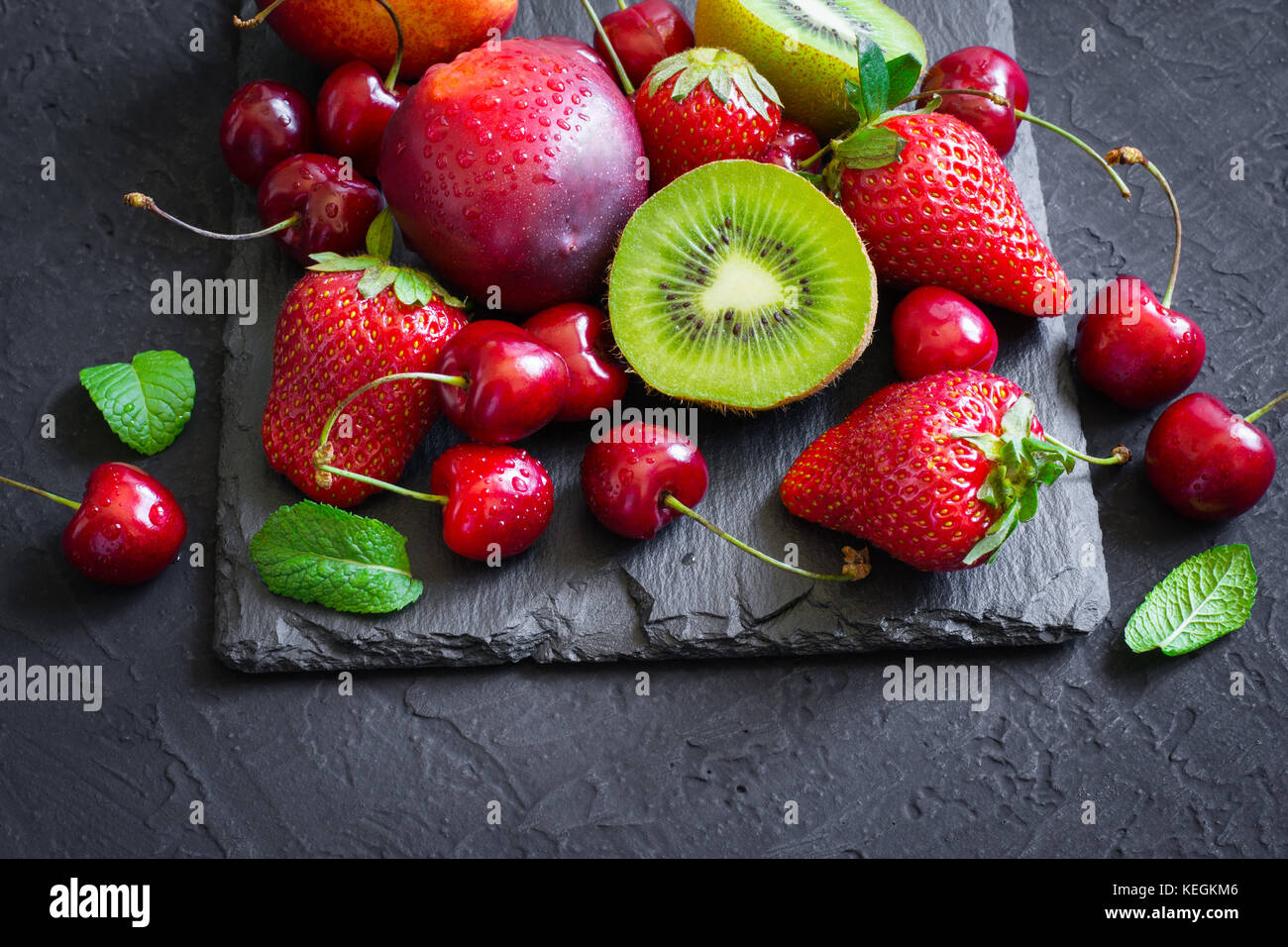 Assorted of Juicy summer fruits and berries. Strawberry, cherry, kiwi and peaches on black slate plate. - Stock Image