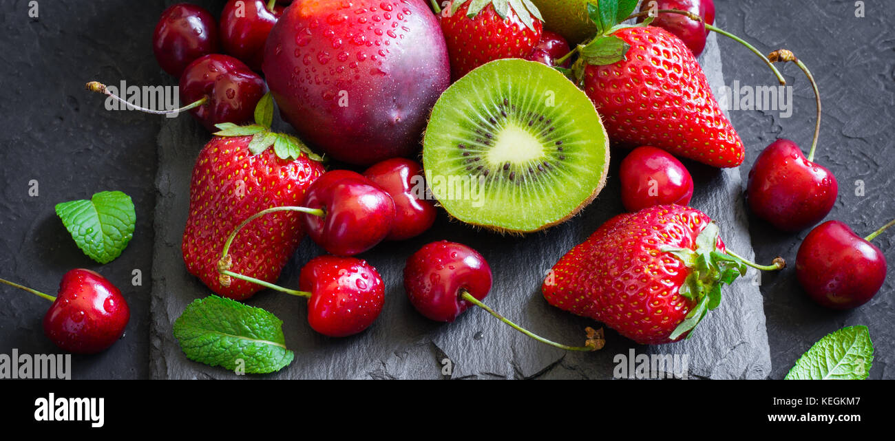Strawberry, cherry, kiwi and peaches on black slate plate. Long banner format - Stock Image