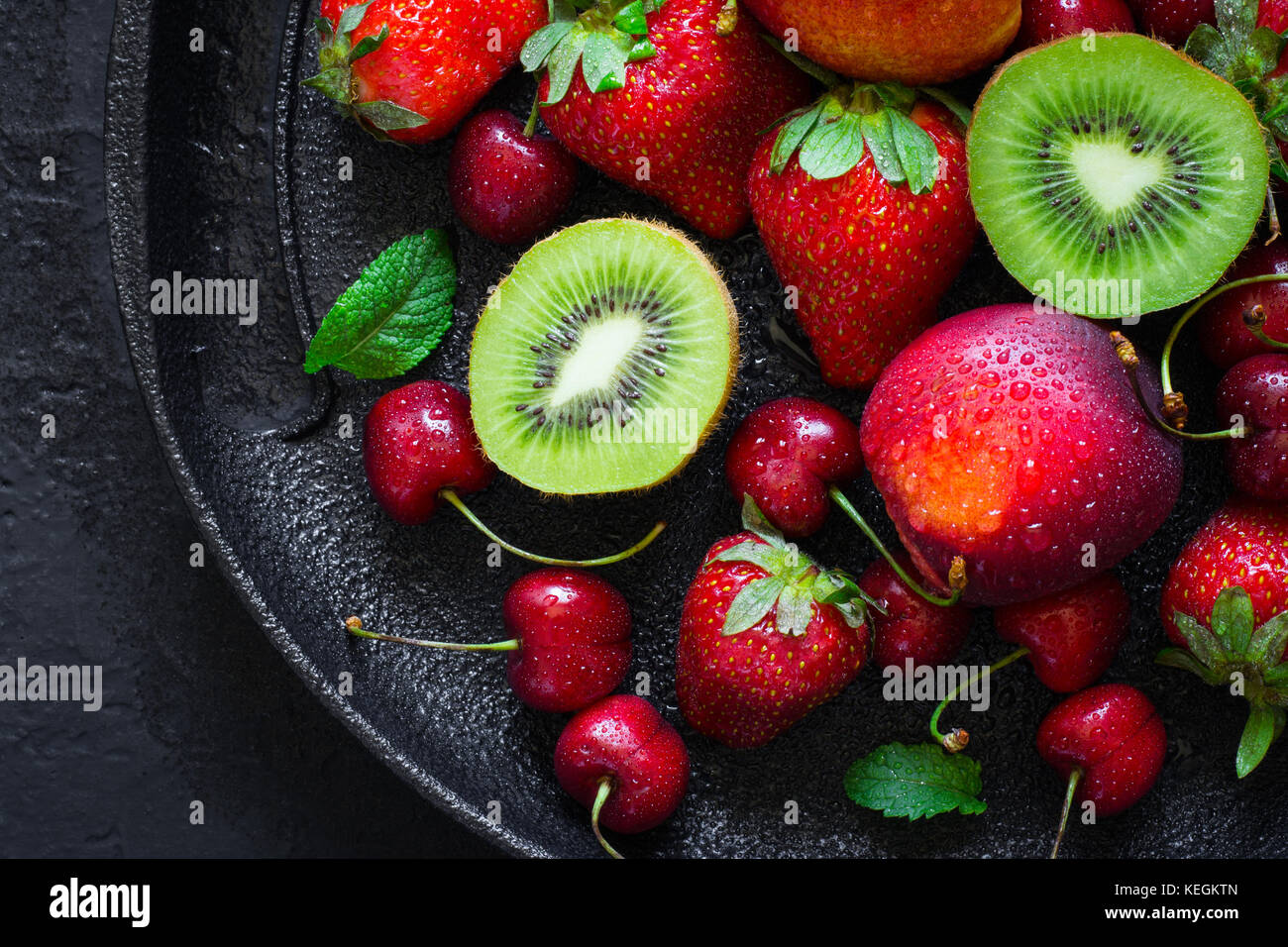 Summer juicy ripe Strawberry, cherry, kiwi and peaches On a black plate closeup. - Stock Image