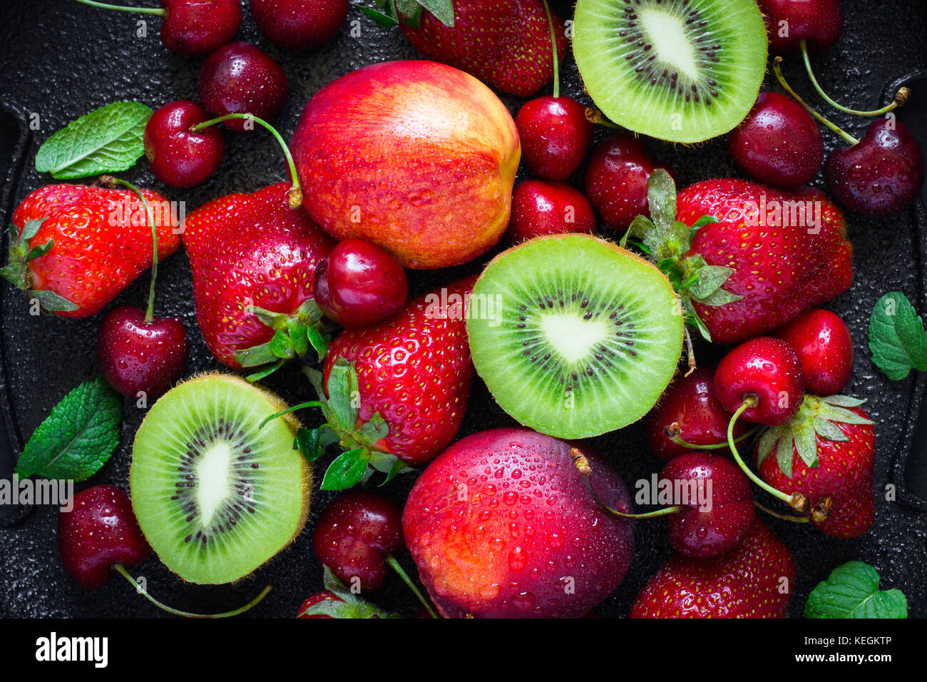 Summer juicy ripe Strawberry, cherry, kiwi and peaches On a black background closeup. Top view - Stock Image