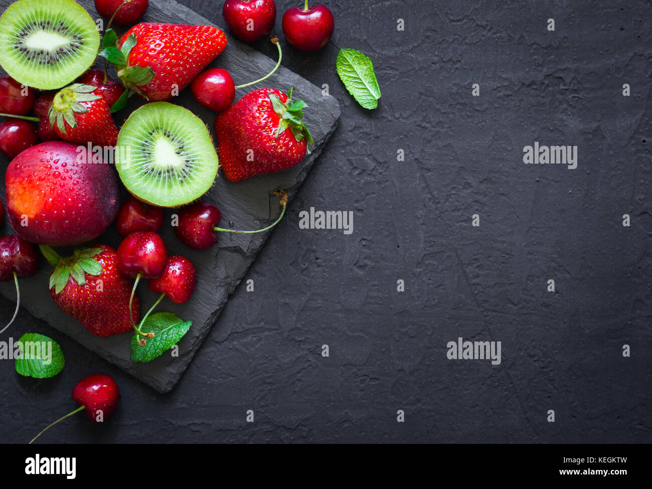 Mix of Juicy summer fruits and berries. Strawberry, cherry, kiwi and peaches on black slate plate. Top view with - Stock Image