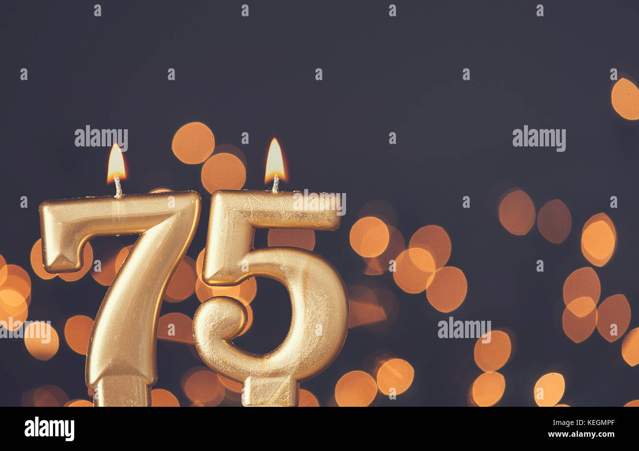 Gold Number 75 Celebration Candle Against Blurred Light Background