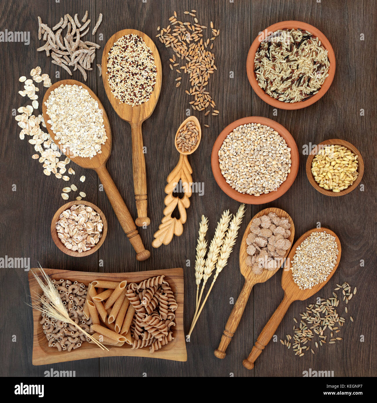High fiber health food of whole wheat pasta, cereal and grains in bowls and spoons on rustic oak background. - Stock Image