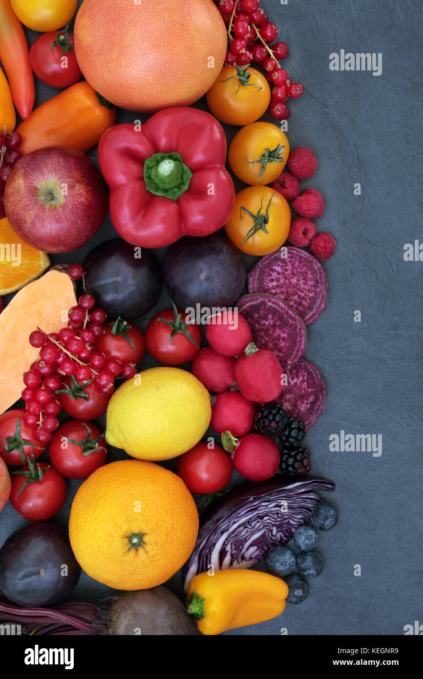 Healthy super food background border with fruit and vegetable selection on slate, high in antioxidants, anthocyanins - Stock Image