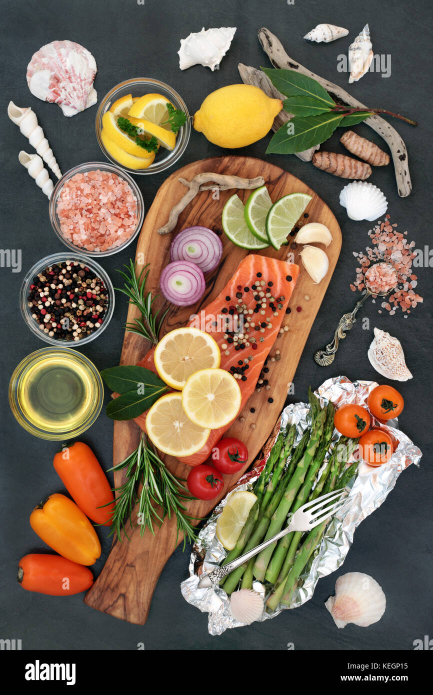 Health food for a healthy heart with fresh salmon fish, seasoning, vegetables, fruit and olive oil on an olive  - Stock Image