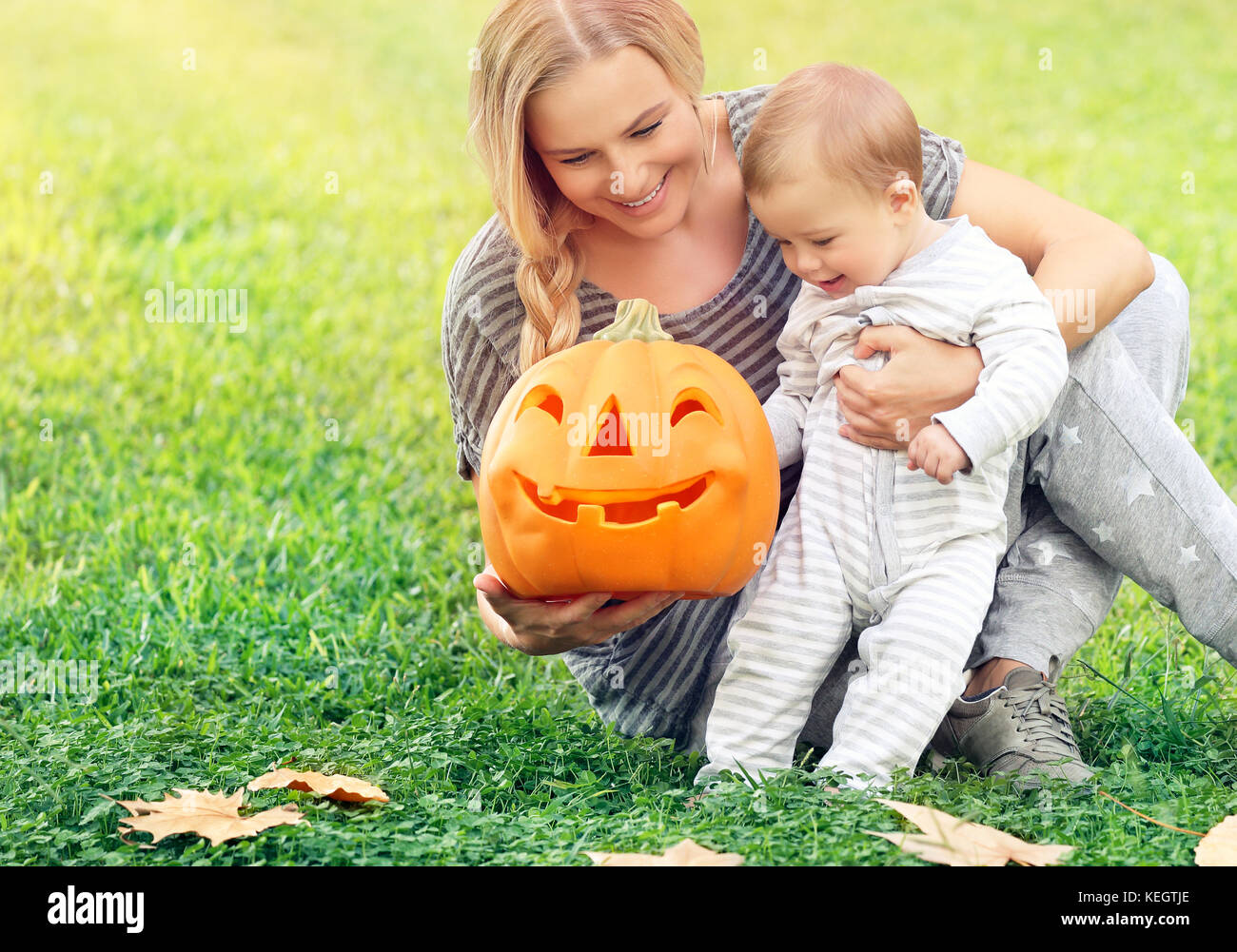 Happy mother with little baby outdoors, sitting on the green grass field and playing with orange carved pumpkin - Stock Image