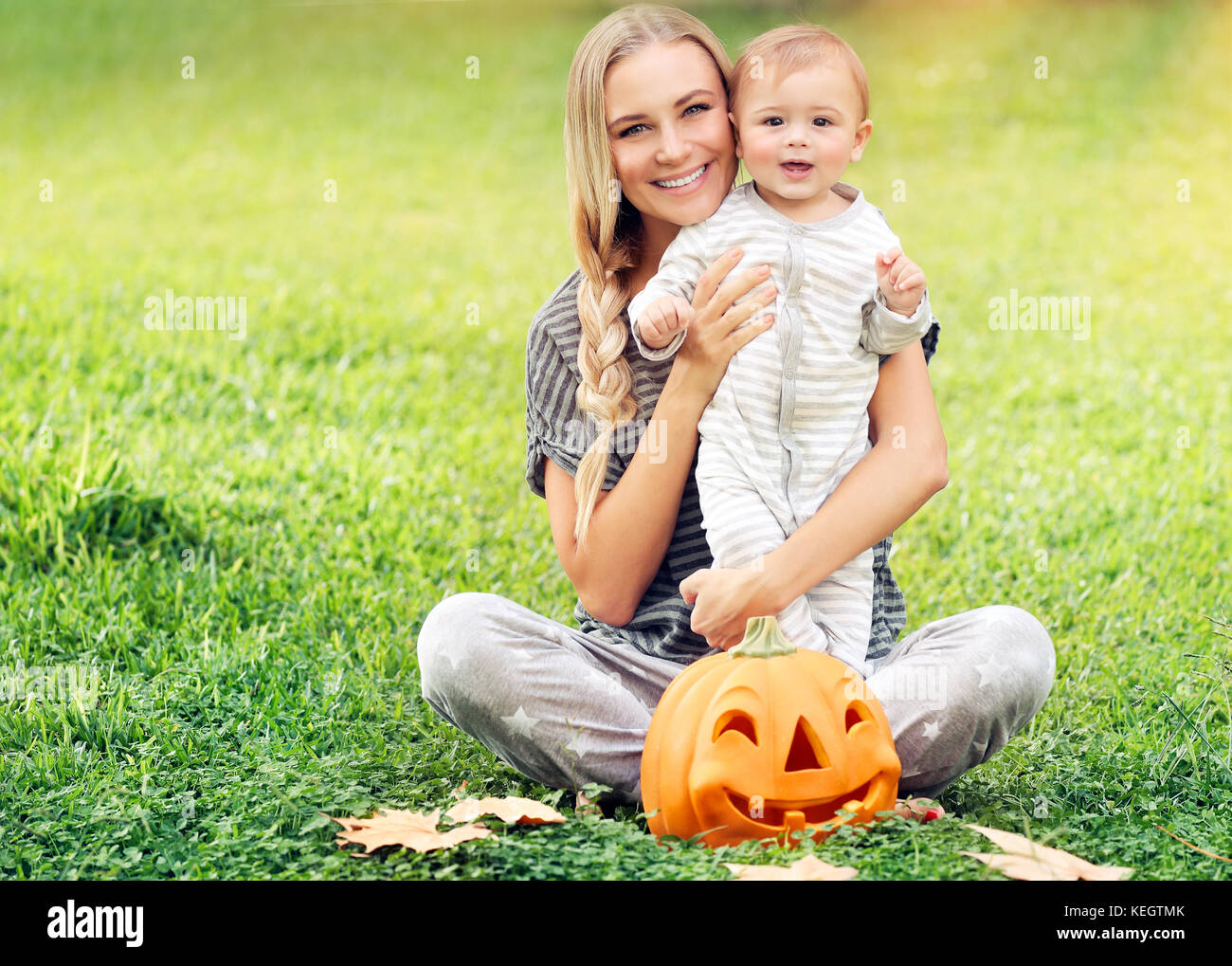 Mother with baby enjoying Halloween holiday outdoors, sitting on fresh green grass field, traditional festive decoration, - Stock Image