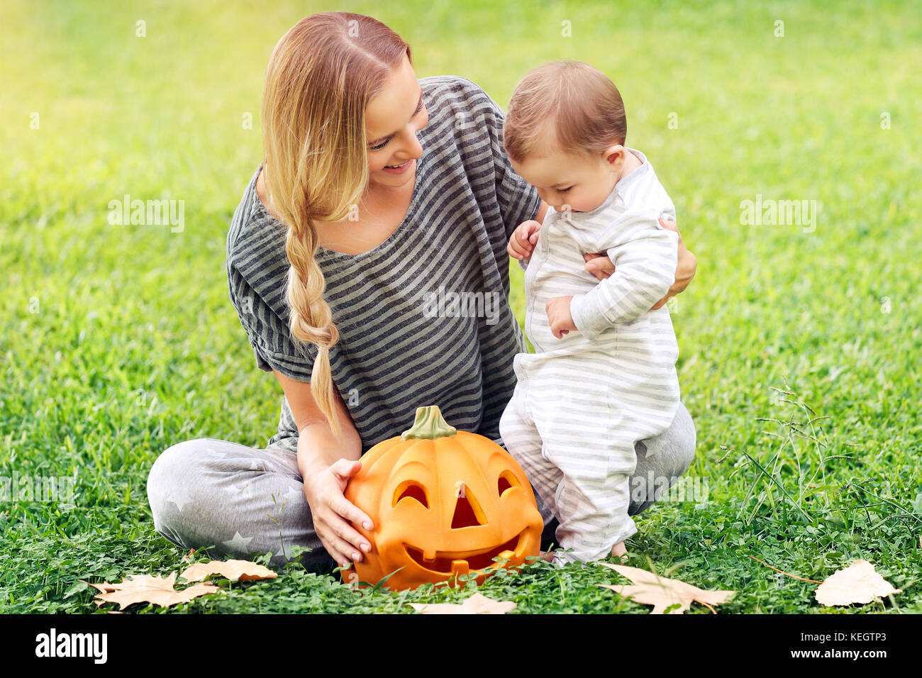 Happy family celebrating Halloween outdoors, mother with cute little baby boy playing with carved pumpkin on the - Stock Image