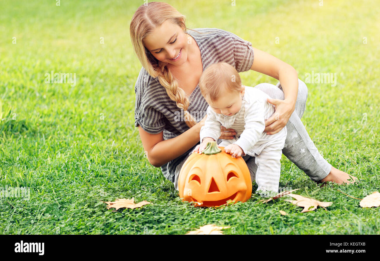 Beautiful young mother with adorable little child, playing with carved pumpkin, enjoying traditional autumn holiday, - Stock Image
