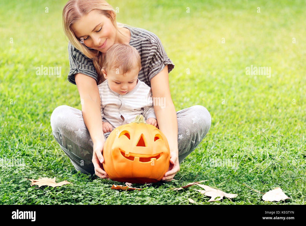 Beautiful young mother with adorable little child, playing with carved pumpkin, enjoying traditional autumn holiday, Stock Photo