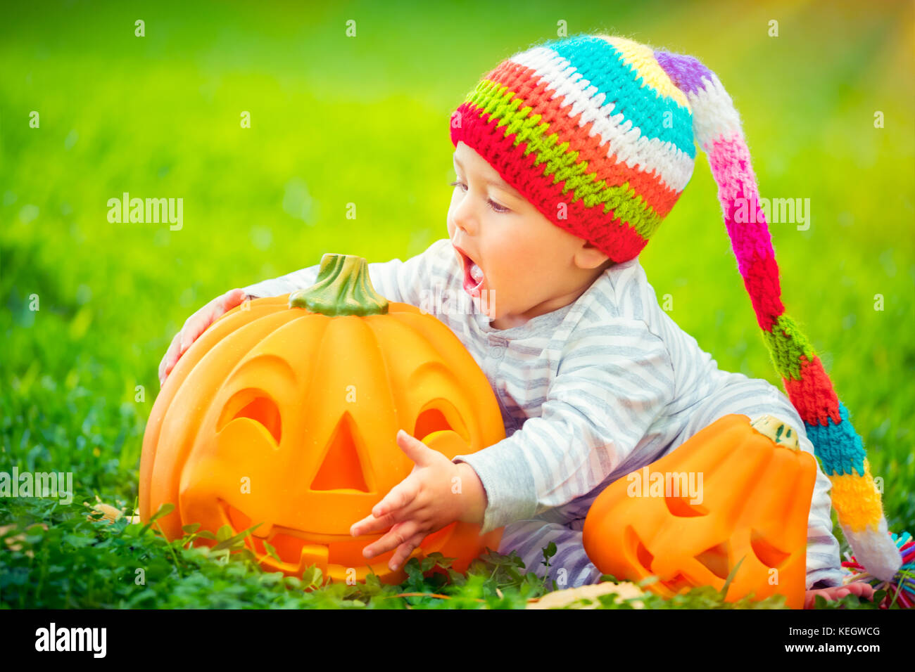 Cute little baby boy wearing funny colorful hat trying to bite beautiful carved festive pumpkin, playing outdoors - Stock Image