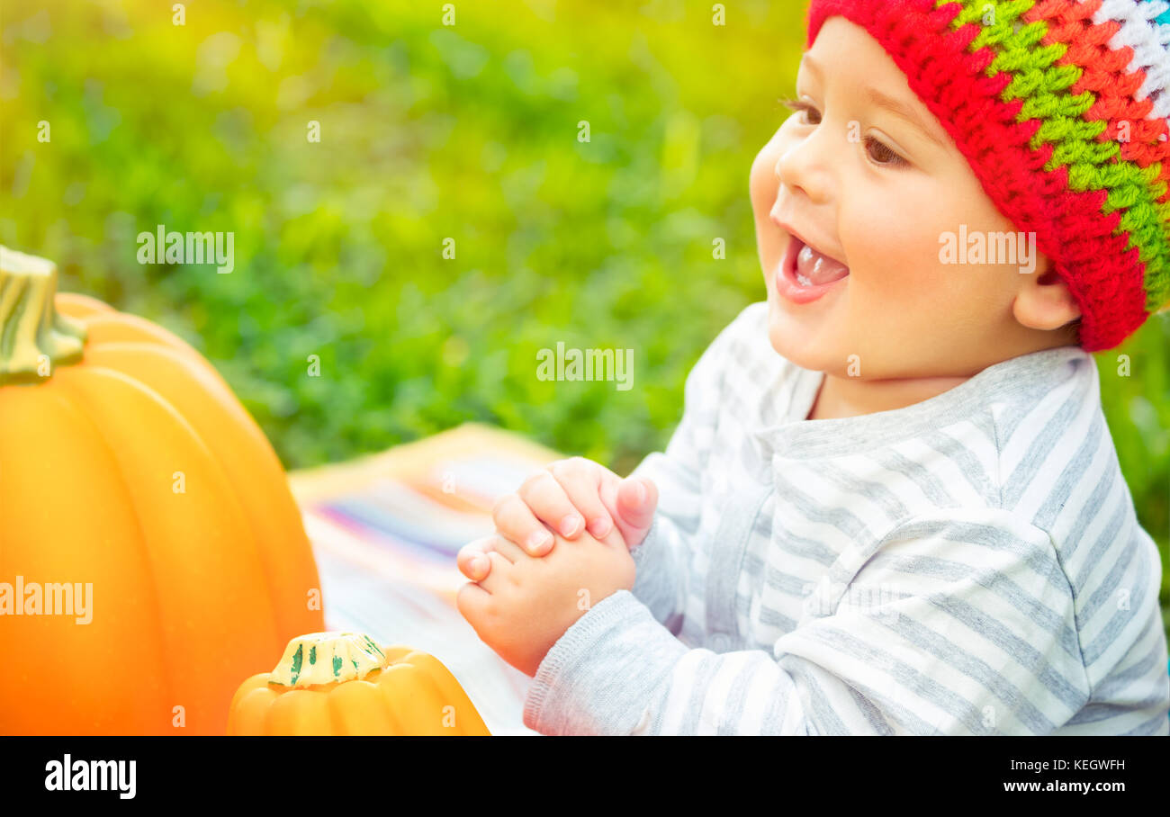 Closeup portrait of a nice cheerful baby boy laughing and enjoying time spending outdoors, sitting near two pumpkins, - Stock Image