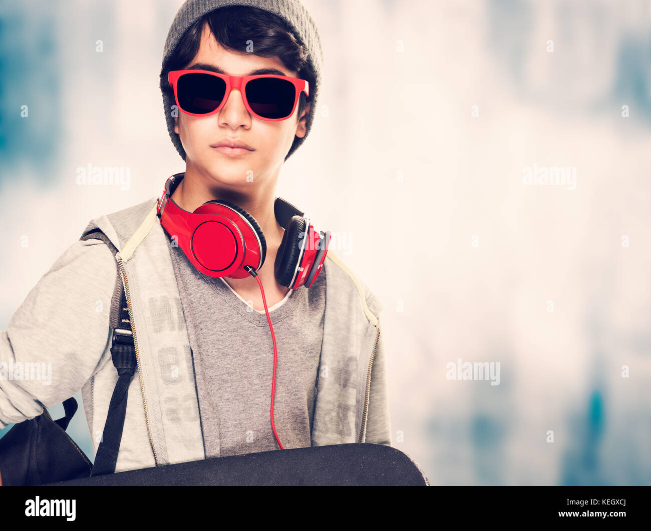 9776a32a61dc Portrait of a stylish teen boy wearing sunglasses and hat holding in hand  skateboard over grunge