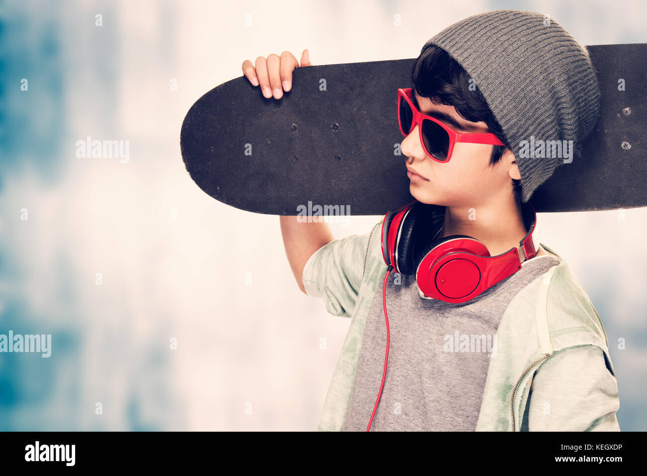 Portrait of a stylish teen boy wearing sunglasses and hat holding in hand skateboard over grunge background, modern Stock Photo